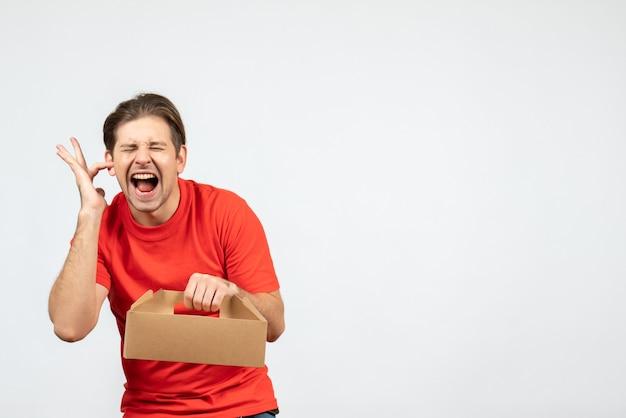 Vista dall'alto del giovane nervoso ed emotivo in camicetta rossa che tiene la scatola chiudendo un orecchio su sfondo bianco