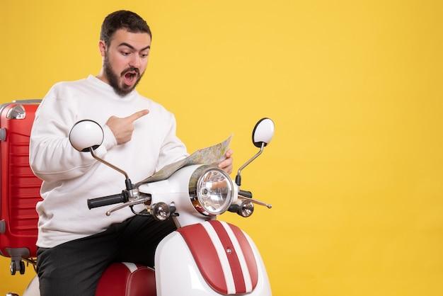 Vista dall'alto di un ragazzo nervoso seduto in moto con la valigia sopra che tiene la mappa su sfondo giallo isolato