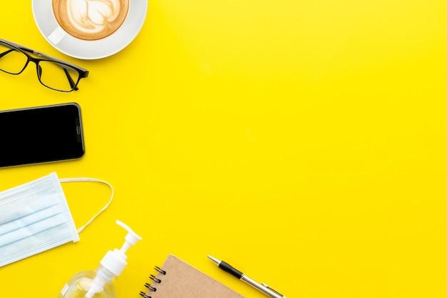 トップビューの新しい予防マスク、眼鏡、スマートフォン、手の消毒剤ジェル、コーヒーカップ、本。コロナウイルス病(covid-19)または健康の概念