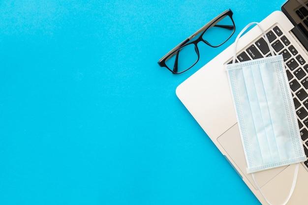 トップビューノートパソコンと眼鏡の新しい予防マスク。コロナウイルス病(covid-19)または健康の概念