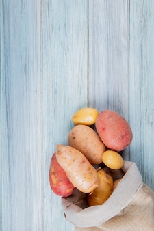 Top view of new russet and red potatoes spilling out of sack on wooden surface with copy space