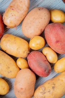 Vista superiore di nuove patate bianche e gialle rosso ruggine su superficie di legno
