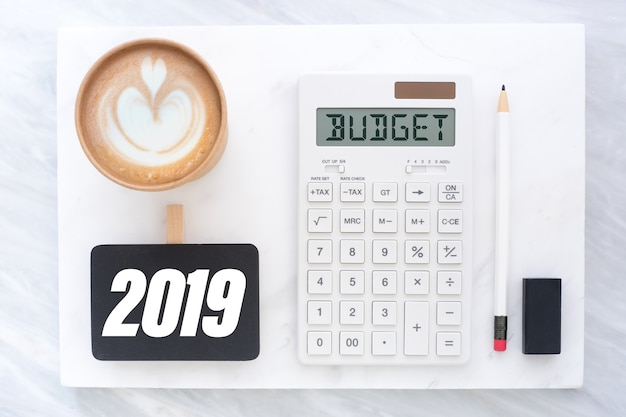Top view of new year 2019 budget on calculator and coffee cup on white marble block