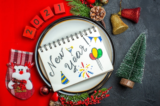 Top view of new year background with dinner plate decoration accessories fir branches and numbers on a red napkin next to christmas tree on a black table