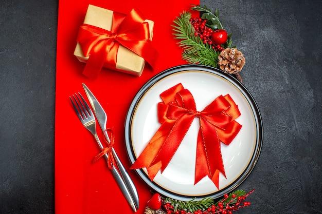 Vista dall'alto dello sfondo del nuovo anno con il nastro rosso sul piatto della cena set di posate accessori per la decorazione rami di abete accanto a un regalo su un tovagliolo rosso