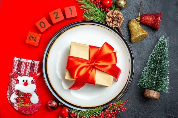 Vista dall'alto dello sfondo di capodanno con il nastro rosso sulla decorazione del piatto della cena accessori rami di abete e numeri calza di natale su un tovagliolo rosso accanto all'albero di natale su un tavolo nero