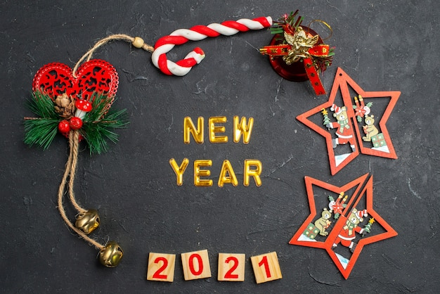 Top view new year in a circle of different xmas ornaments candy wood block on dark isolated surface