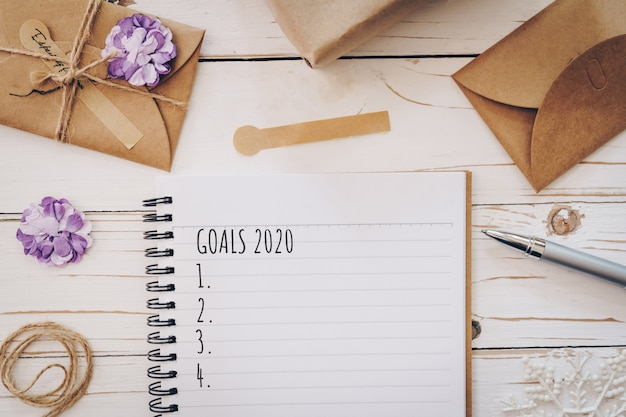 Top view of new year goals 2020 list empty note pad and christmas card on wooden table with xmas decoration.