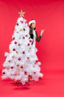 Vista dall'alto dell'umore del nuovo anno con una bella ragazza in un abito nero con il cappello di babbo natale che si nasconde dietro l'albero di natale