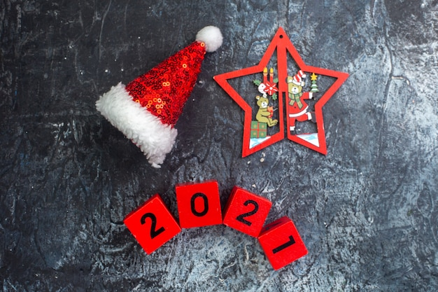 Top view of new year mood with santa claus hat numbers and star with christmas drawings on dark surface