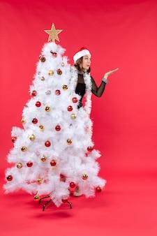 Vista dall'alto dell'umore del nuovo anno con una bella ragazza scioccata in un abito nero con il cappello di babbo natale che si nasconde dietro l'albero di natale