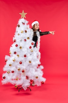Top view of new year mood with smiling beautiful girl in a black dress with santa claus hat hiding behind christmas tree