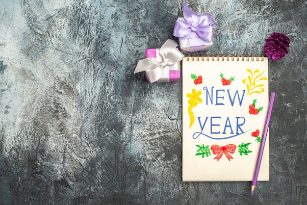 Top view of new year note with pencil and little presents on grey surface