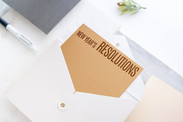 Top view of new year's resolutions on gold card in envelope with paper and pen