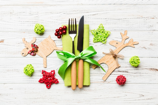 Top view of new year utensils on napkin with holiday decorations and reindeer. close up of christmas dinner concept