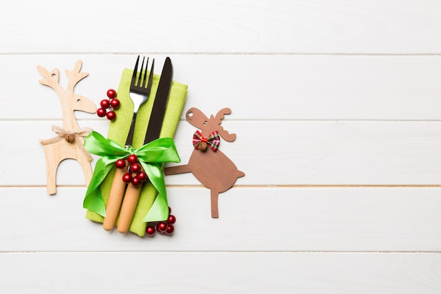 Top view of new year utensils on napkin with holiday decorations and reindeer on wooden background. christmas dinner  with copyspace