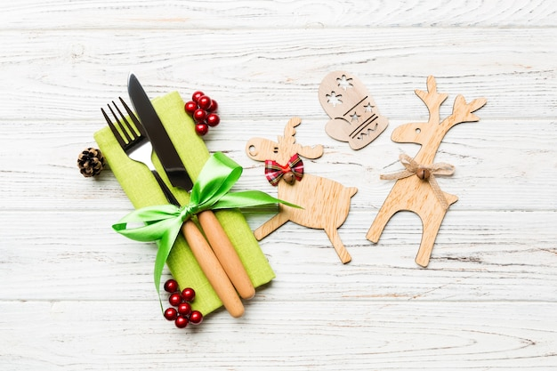 Top view of new year utensils on napkin with holiday decorations and reindeer on wooden background. close up of christmas dinner concept .