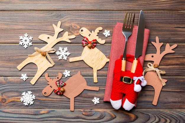 Top view of new year utensils on napkin with holiday decorations and reindeer on wooden surface