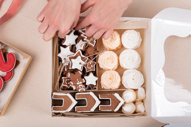 Top view new years sweets in gift wrapping. tasty glazed painted cookies and marshmallow and female hands
