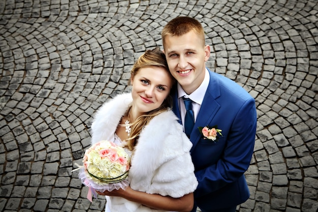Top view of a newly-married couple, close-up portrait, on a background of cobblestones.