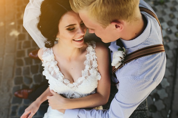 Top view of newlyweds laughing and hugging