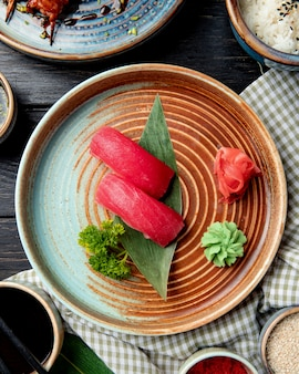 Top view of nigiri sushi with tuna on bamboo leaf served with pickled ginger slices and wasabi on a plate
