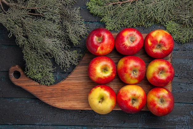 Top view nine fruits nine yellow-reddish apples on a wooden cutting board on grey table between tree branches