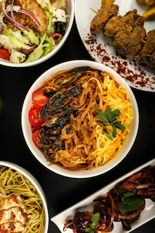 Top view noodles with fried vegetables with tomatoes salad and other dishes on the table