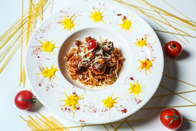 Top view noodles with meat grated cheese and tomatoes