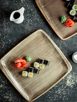 Top view of nori sushi with avocado served with ginger and wasabi