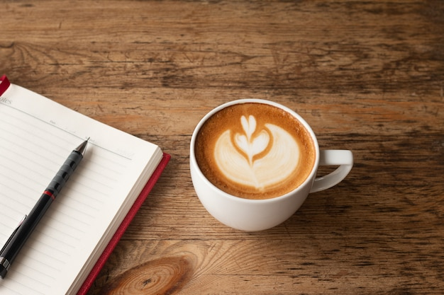 トップビュー鉛筆でノートブック、ビジネスのための木製テーブルにコーヒーのカップ背景