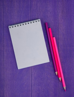 Top view of note pad and colored pencils on purple background with copy space
