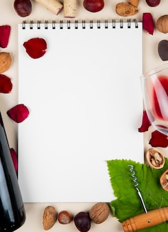 Vista dall'alto del blocco note con bottiglia di vino rosso mandorle noci olive cavatappi e petali di fiori intorno su sfondo bianco con spazio di copia