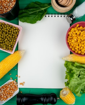 Top view of note pad with corns corn seeds green peas spinach lettuce and salt around on green with copy space