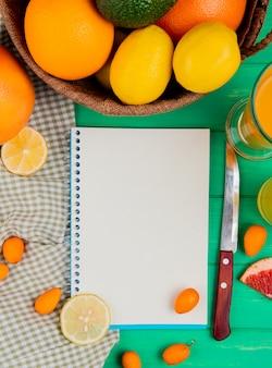 Vista superiore del blocco note con il coltello e il succo arancio del kumquat del limone intorno su fondo verde con lo spazio della copia