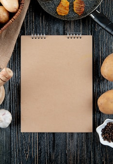 Top view of note pad with vegetables potato chips black pepper around on wooden background with copy space