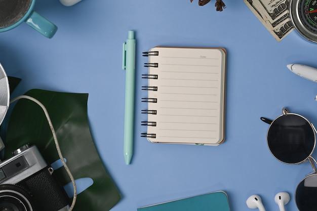Блокнот сверху и личные аксессуары на синем фоне.