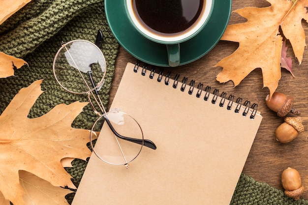 Top view of notebook and autumn leaves with glasses