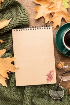 Top view of notebook and autumn leaves