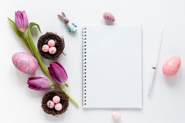 Top view notebook beside flowers and easter eggs