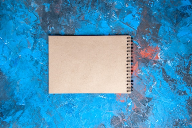 Top view a notebook on blue-red background