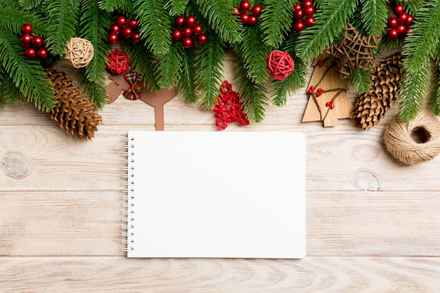 Top view notebook, christmas toys, decorations and fir tree branches on wooden .   holiday