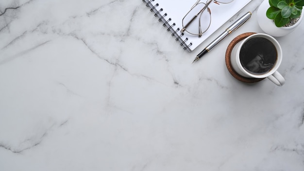 Тетрадь сверху, чашка кофе и очки на мраморной предпосылке.