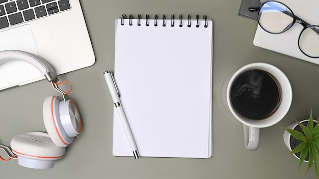 Тетрадь сверху, чашка кофе и наушники на творческой рабочей области.