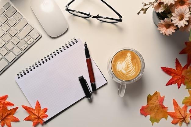 흰색 탁자에 있는 탑 뷰 노트북, 커피 컵, 안경, 단풍나무 잎.