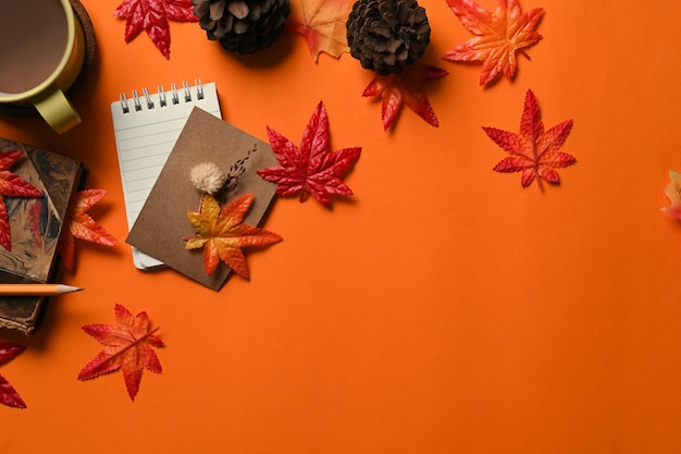 상위 뷰 노트북, 커피 컵, 소나무 콘, 단풍나무 잎이 주황색 배경에 있습니다.