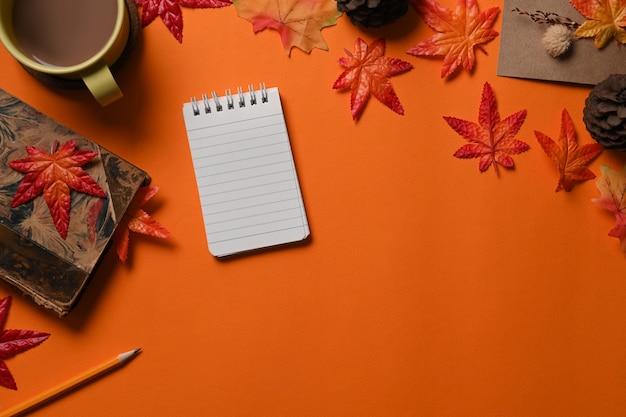 탑 뷰 노트북, 커피 한 잔, 소나무 콘, 단풍나무 잎이 주황색 배경에 있습니다.