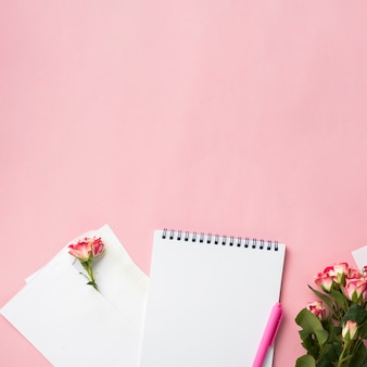 Top view on notebook on desk with bouquet of roses and copy space