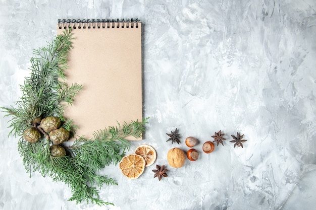 Top view notebook dried lemon slices anises pine tree branches on grey background with copy space