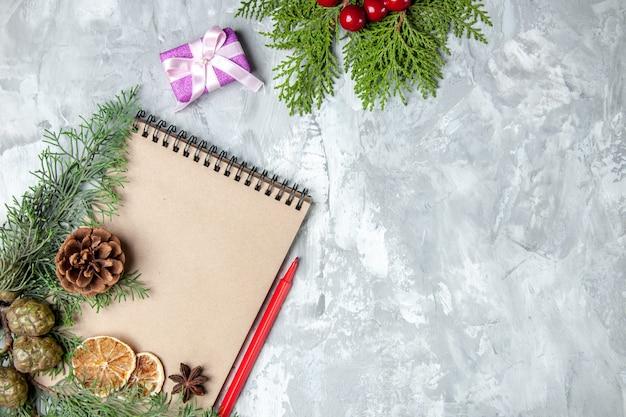 Notebook vista dall'alto fette di limone essiccate anice rami di pino matita rossa su sfondo grigio spazio libero